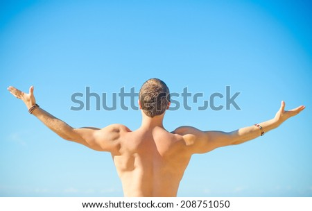 Muscular attractive man near the sea. Freedom concept.