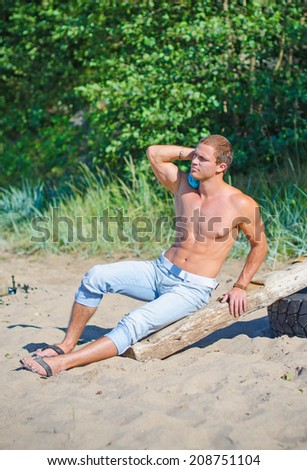 Muscular attractive man resting on the beach. - stock photo
