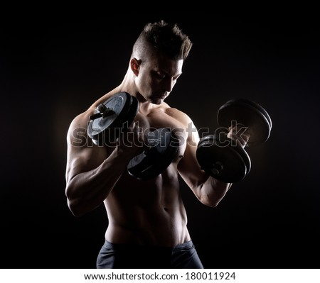 Muscular attractive man weightlifting on dark background. - stock photo