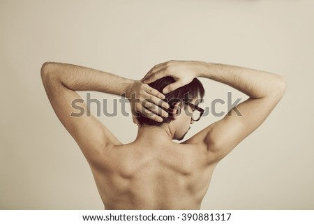 Muscular back of young man wearing glasses on white
