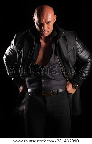 muscular bald man posing in a jacket on a black background - stock photo