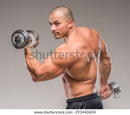 Muscular bald man posing with weights on a gray background. - stock photo