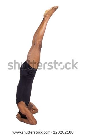 muscular black man doing upside down yoga on white background - stock photo