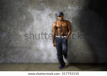 Muscular black man modeling jeans and shirtless torso on urban concrete wall.  The background is a grunge concrete alley wall. - stock photo