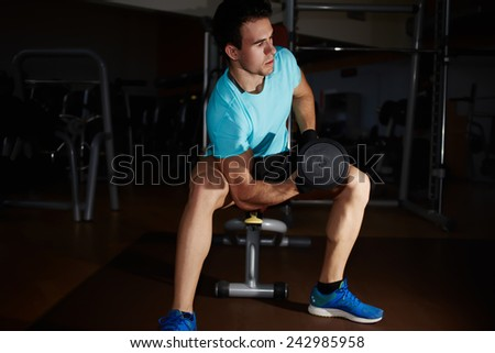 Muscular body builder lifting weights in the gym, attractive strong man working out with biceps at fitness center - stock photo