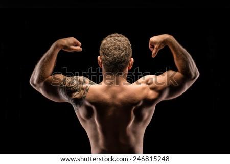 Muscular body builder posing back view - stock photo
