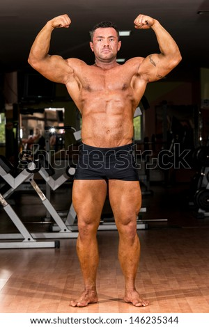 muscular body builder showing his front double biceps - stock photo