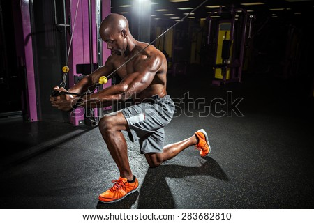 Muscular body builder working out  at the gym doing chest fly exercises on the cable wire machine.