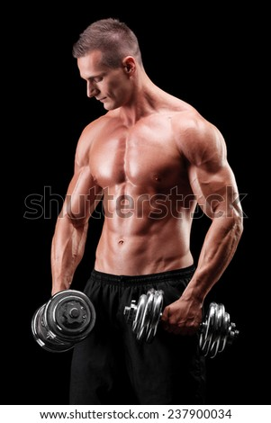 Muscular bodybuilder exercising with two weights on black background