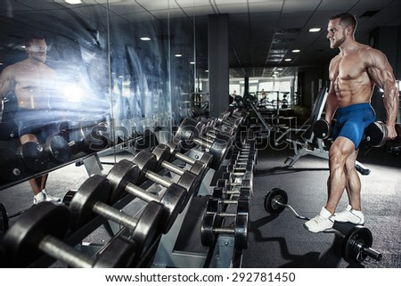 Muscular bodybuilder guy doing exercises with dumbbell in gym - stock photo
