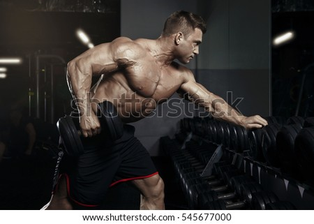 Muscular bodybuilder guy doing exercises with dumbbell in gym. Handsome power athletic man in training pumping up muscles with dumbbell