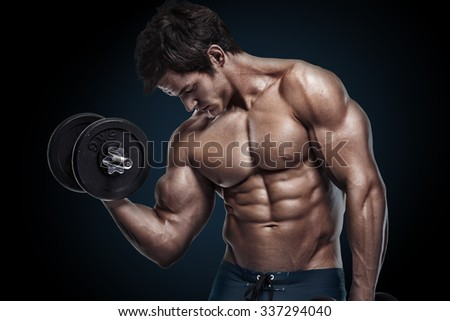 Muscular bodybuilder guy doing exercises with dumbbells isolated over black background - stock photo
