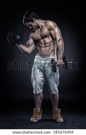 Muscular bodybuilder guy doing exercises with dumbbells over black background - stock photo