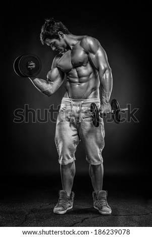 Muscular bodybuilder guy doing exercises with dumbbells over black background - stock photo