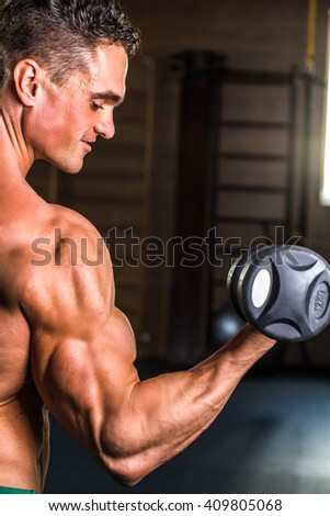 Muscular bodybuilder guy doing exercises with dumbbells.Strong Athletic Man Fitness Model Torso showing six pack abs.Strong Athletic Man Fitness Model Torso showing big muscles - stock photo