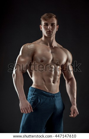 Muscular bodybuilder guy doing posing over black background