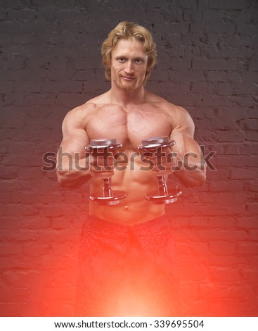 Muscular bodybuilder man. Man with large muscles of the body on a gray brick wall background. Bodybuilder. Working out biceps. Two dumbbells. Strong man holding a dumbbell. Copy space for text. Poster - stock photo
