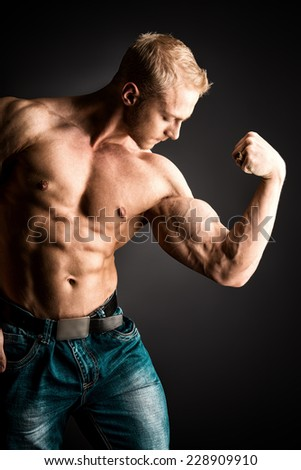 Muscular bodybuilder man posing over dark background. Men's beauty. Sports.  - stock photo