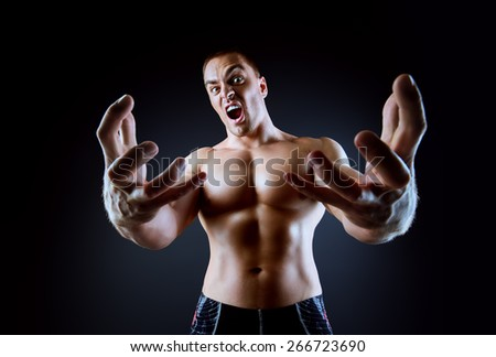 Muscular bodybuilder man stretching his arms to the camera and shouting over black background. - stock photo