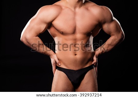 Muscular bodybuilder's big torso. Huge torso of young athlete. Best front pose. Few weeks before competition. - stock photo