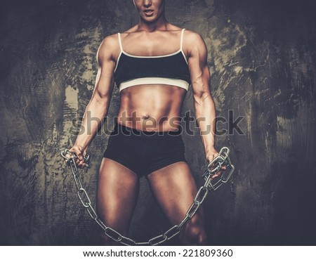 Muscular bodybuilder woman holding chains - stock photo