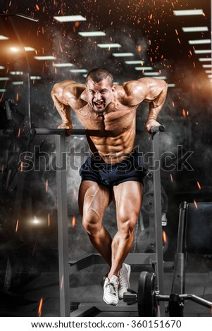 Muscular bodybuilder working out in gym doing exercises on parallel bars. Athlitic male naked torso - stock photo
