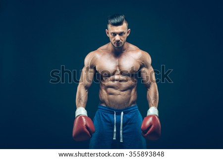 Muscular boxer in studio shooting, on black background - stock photo