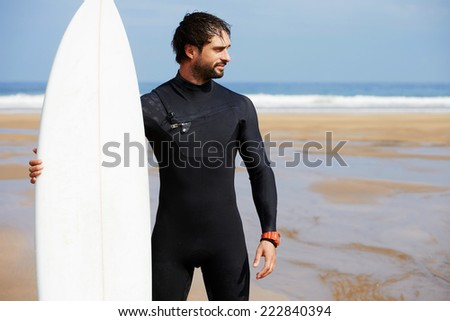 Muscular build surfer holding his surfing board standing on ocean beach with big waves in background, young surfer standing on a beach with his surfboard and looking along the shore, healthy lifestyle - stock photo