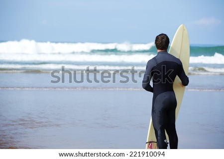 Muscular build surfer standing on the beach enjoying amazing view of ocean, surfer man carrying his surfing board standing against ocean and looking the waves, professional surfer - stock photo