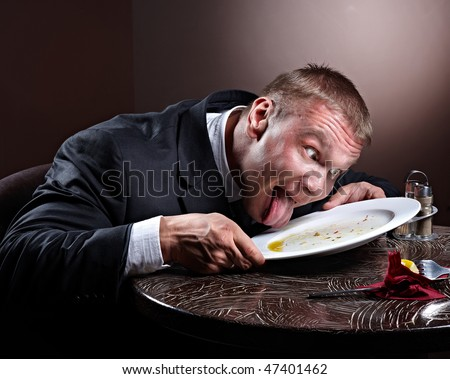 Muscular businessman lick the plate - stock photo