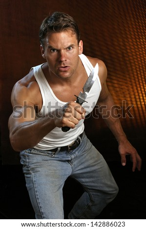Muscular Caucasian man yielding a large survival knife prepares to attack