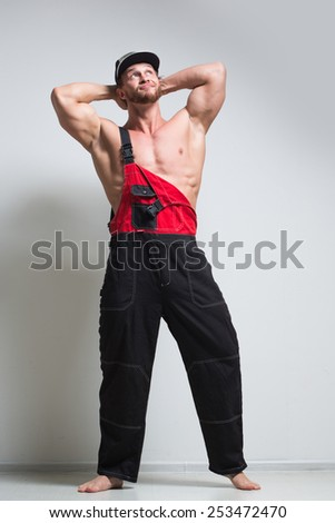 muscular construction worker in overalls - stock photo