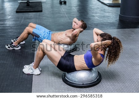 Muscular couple doing bosu ball exercises at the crossfit gym - stock photo