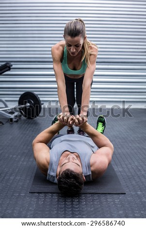 Muscular couple doing core exercises at the crossfit gym - stock photo