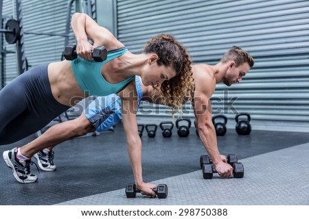Muscular couple doing plank exercise while lifting weights - stock photo