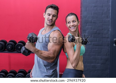 Muscular couple giving back to back while lifting dumbbells - stock photo