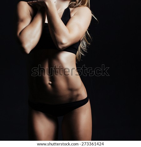 Muscular female body on black background