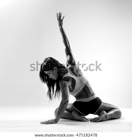 Muscular female body. Young strong athlete posing on grey background. Black-and-white contrast photo