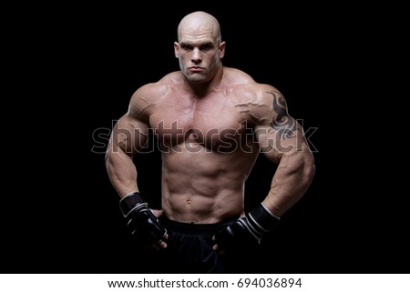 Muscular fighter in front of black background