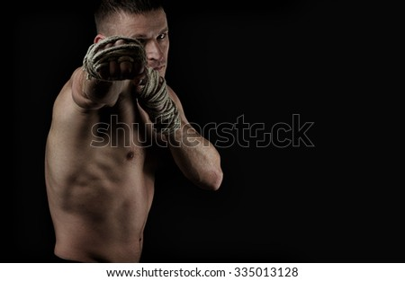 Muscular fighter Muay Thai training on the black background with hemp ropes on hands. Hard light, dark lighting - stock photo