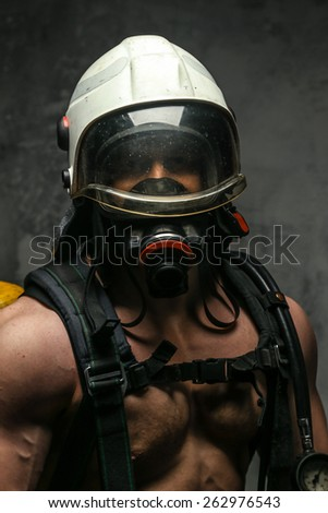 Muscular firefighter in oxygen mask with naked torso on grey background