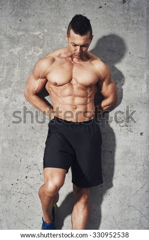 Muscular fit and healthy man standing on grey background, looking down, wearing no shirt and black shorts. Fitness concept abdominal muscles