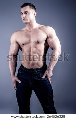 Muscular fit man with perfect body posing in jeans .