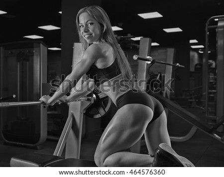 Muscular fitness girl with a beautiful smile posing in the gym