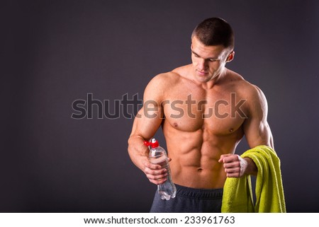 Muscular guy - bodybuilder posing on a gray background. Athletic man holding a bottle of water in hand, a towel around his neck. Sport, health, bodybuilding, strength, power - a concept sports.