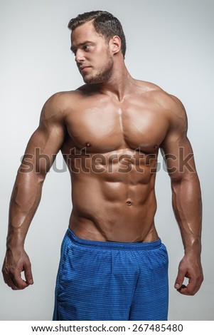 Muscular guy posing in studio on grey background.