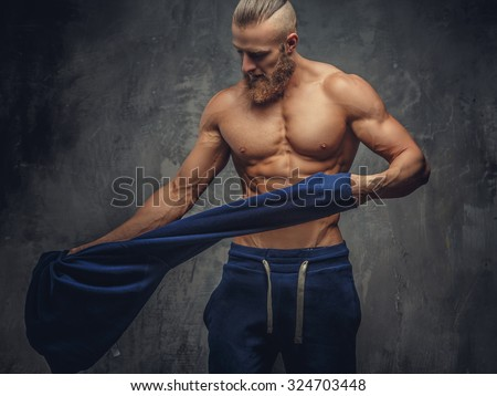 Muscular guy putting out blue sweater.