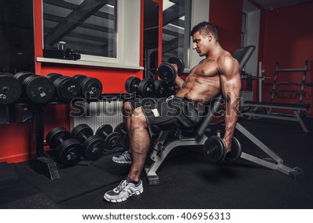 Muscular guy with dumbbells in a gym club.