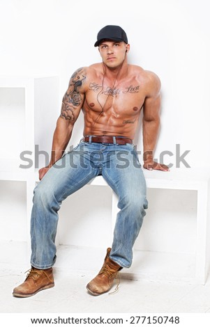 Muscular guy with tattooes in blue jeans - stock photo