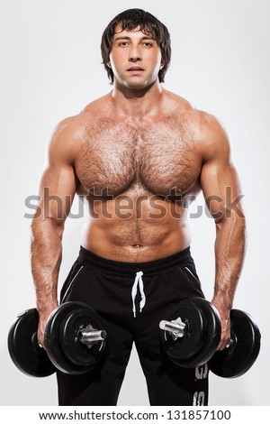 Muscular guy working out with dumbbells isolated over background - stock photo